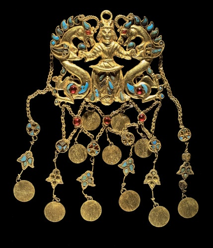 "One of a pair of pendants depicting the ""Dragon Master"" (Tillya Tepe, Tomb II), 1st century BC - 1st century AD (cat. No. 61) gold, turquoise, garnet, lapis lazuli, carnelian and pearl, 5.2 x 6.9 x 1.1 cm (2 1/ 16 x 23/ 4 x 7/ 16); overall length of 2 pendants: 12.1 cm (4 4/ 4); disk diameter: 1.2 cm (1 / 2)  - National Museum of Afghanistan © Thierry Ollivier / Musée Guimet"